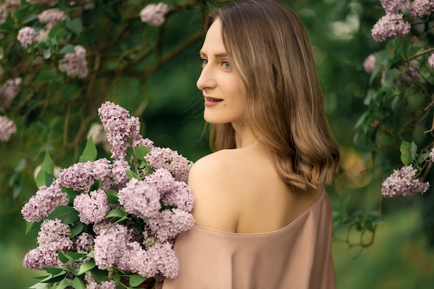 Young woman in a beautiful dress is standing near a lilac bush