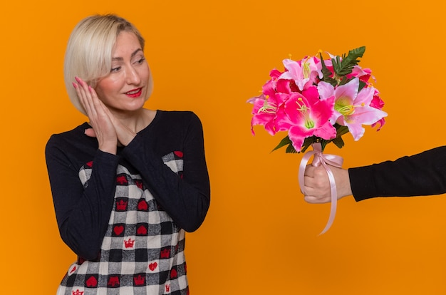 Giovane donna in vestito bello che sembra sorridere felice e sorpreso che tengono le mani insieme che ricevono il mazzo dei fiori che celebrano la giornata internazionale della donna in piedi sopra la parete arancione