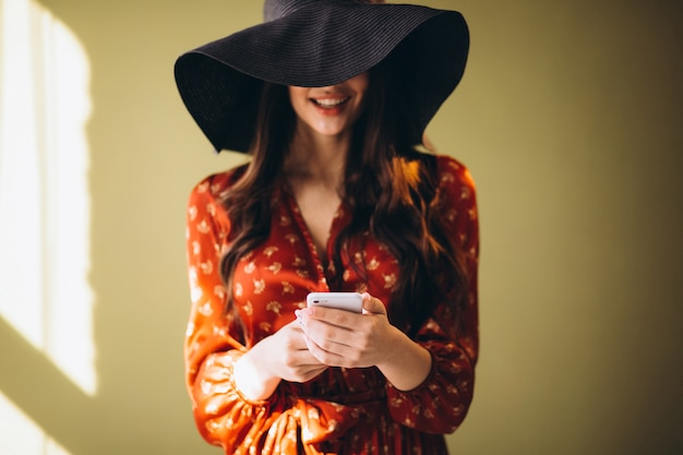 Young woman in a beautiful dress using phone and shopping online