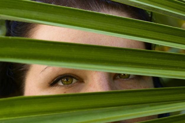 Young woman beautiful green eyes white skin green palm leaf portrait