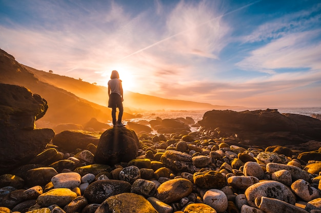 A young woman in the beautiful sunset of mount jaizkibel. basque country