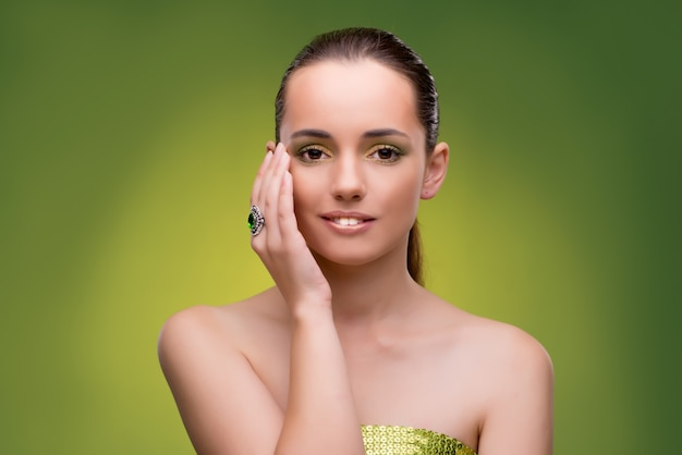Young woman in beauty concept on green wall
