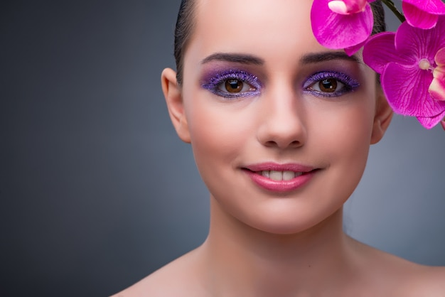 Young woman in beauty concept with orchid flower