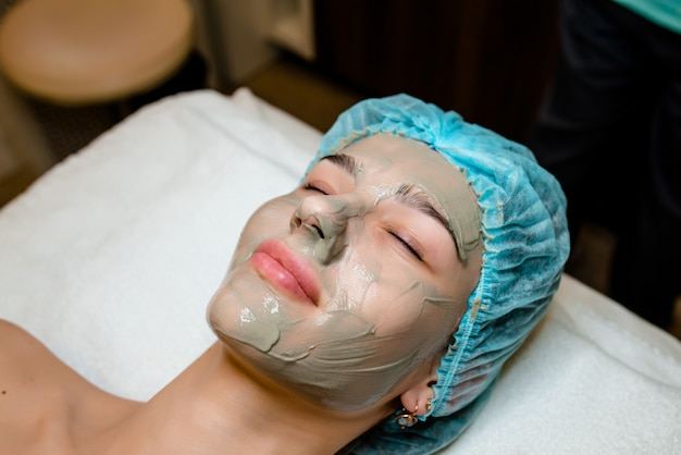 Young woman in beauty salon having face mask