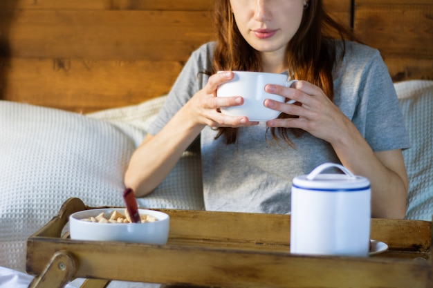 Young woman in bed eating breakfast