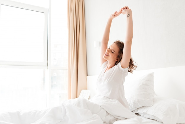 Young woman in bed indoors stretching