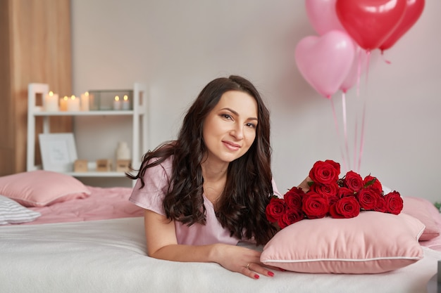 Young woman on bed in pink pajamas with bouquet of red roses