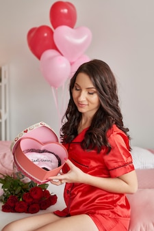 Young woman on bed in red pajamas with heart-shaped gift box
