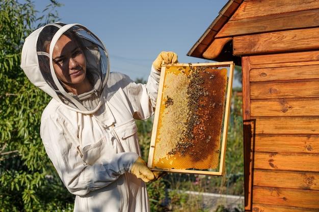 Молодая женщина пасечник держит деревянную рамку с сотами