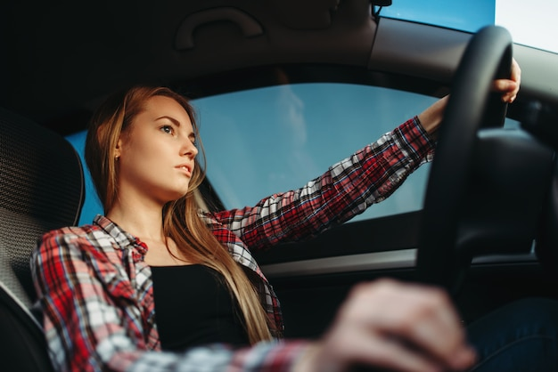 Young woman beginner drives a car