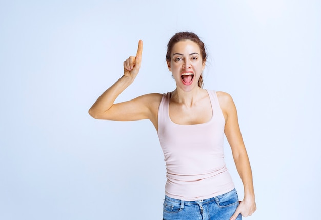 Young woman in beige athlete pointing at something upside