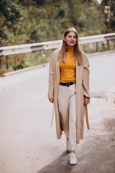 Young woman in beige coat walking in park