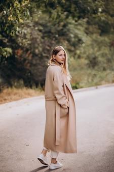Giovane donna in cappotto beige che cammina nel parco