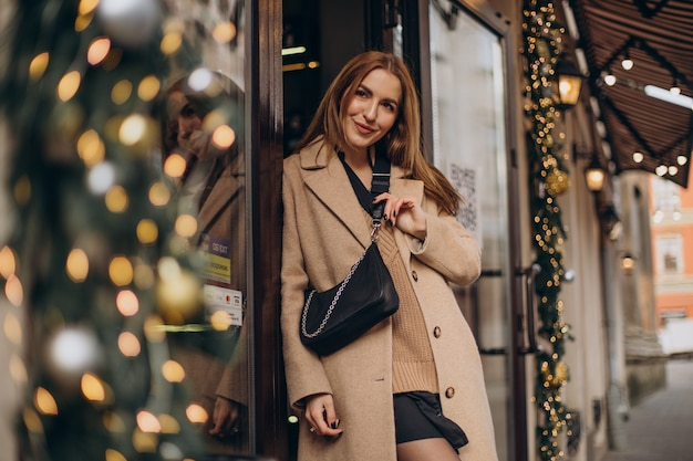Young woman in beige coat walking in the street on christmas