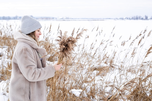 A young woman in a beige dress of neutral colors collects pampas grass Premium Photo