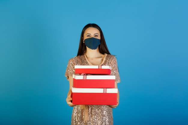 Young woman in beige dress with sequins in protective blue mask is holding three red-white gift boxes,