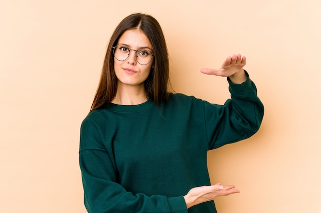 Young woman on beige holding something with both hands, product presentation.