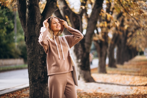 Young woman in beige suit outside in an autumn park