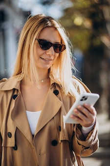 Young woman in beige trench using phone outside