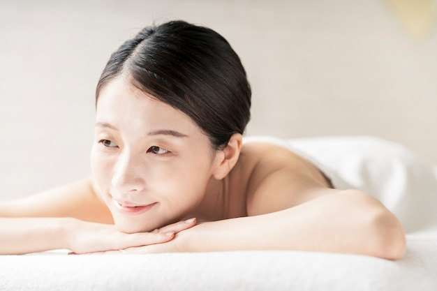Молодая женщина получает массаж в салоне красоты с яркой атмосферой