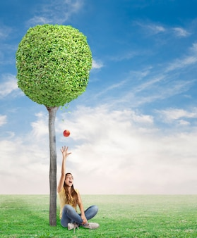 젊은 여자는 나무 아래 빨간 사과에 놀라