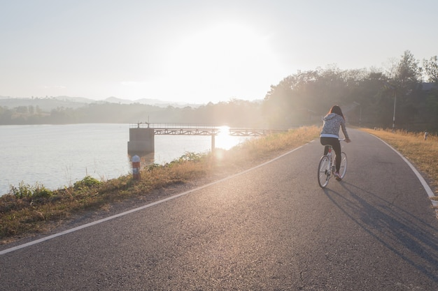 Young woman bicycling on load dam in morning