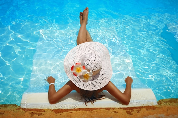 Young woman in big white hat rested on a lounger in the pool