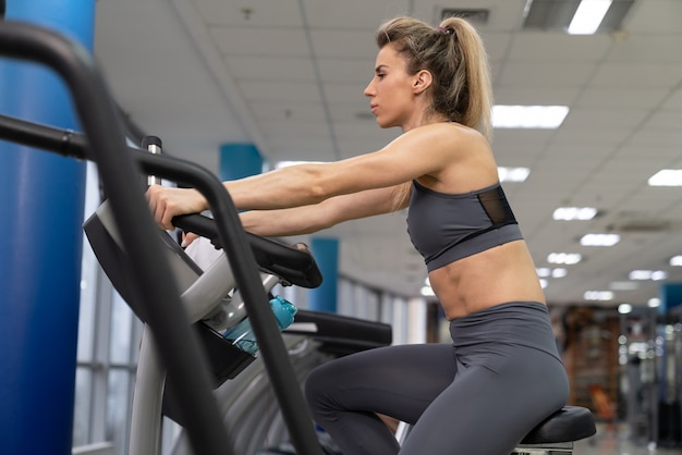 Young woman on bike at gym