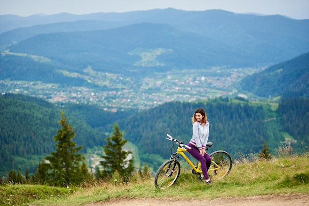 Young woman biker sitting on yellow bike near rural trail on the top of the mountain on cloudy evening