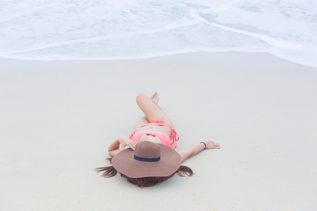 Young woman in a bikini lying on the sand beach and waves, young woman sunbathing and relaxing on the white sandy beach, summer travel concept.