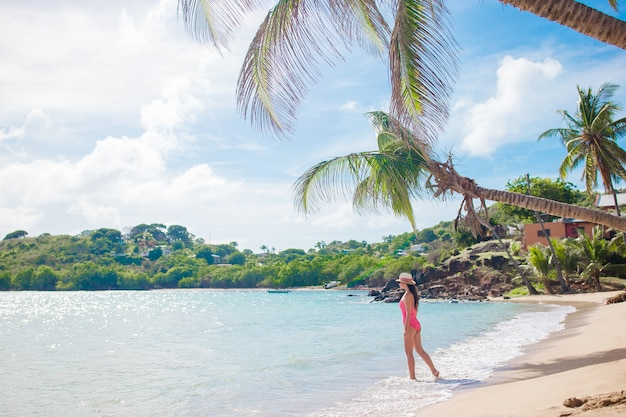 Young woman in bikini and straw hat on tropical beach. beautiful girl under the palm tree on tropical carlisle bay beach with white sand and turquoise ocean water at antigua island in caribbean