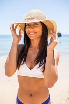 Giovane donna in bikini che indossa il cappello di paglia bianco godendo le vacanze estive in spiaggia. ritratto di bella donna latina rilassante in spiaggia con occhiali da sole.