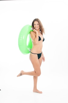 Young woman in bikini with a float and prepared for the beach on white background