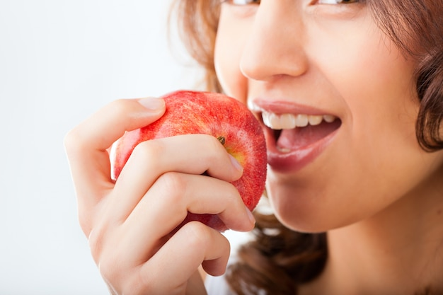 Young woman bites in a apple