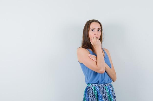 젊은 여자는 일 중항, 치마에 감정적으로 주먹을 물고 무서워, 전면보기.