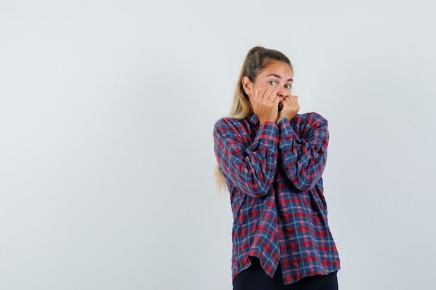 Giovane donna che morde i pugni in camicia controllata e che sembra spaventata