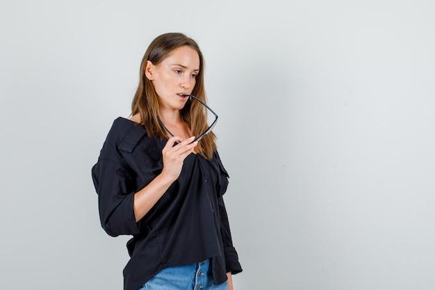 Giovane donna che morde gli occhiali mentre pensa in camicia, pantaloncini vista frontale.