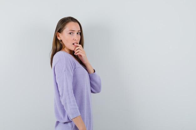 ライラックのブラウスで指を噛んで印象的な若い女性。 。テキスト用のスペース