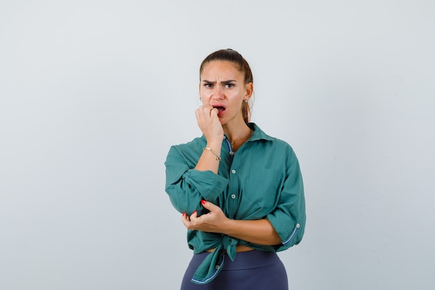Young woman biting nails emotionally in green shirt and looking troubled. front view.