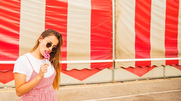 Young woman biting red lollipop standing in front of tent