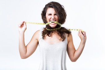 Young woman biting tape measure over white background.