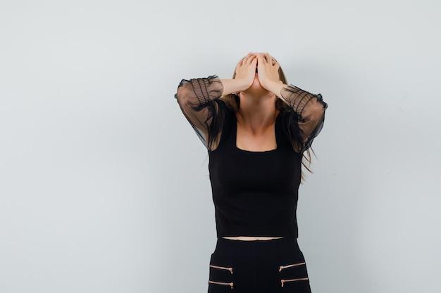 Giovane donna in camicetta nera e pantaloni neri che copre il viso con le mani e sembra dispiaciuto