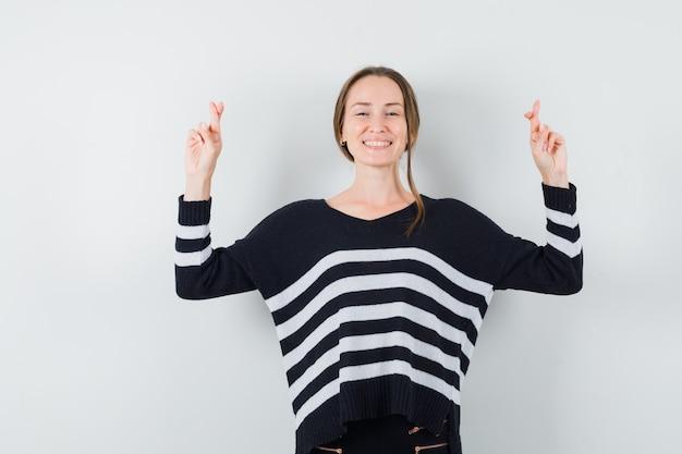 Giovane donna in camicetta nera e pantaloni neri tenendo le dita incrociate e guardando felice
