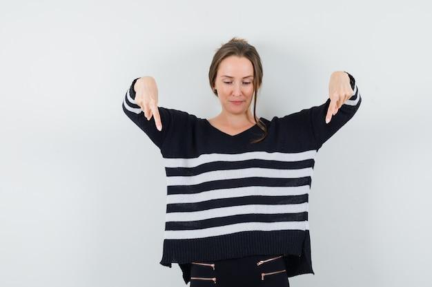 Giovane donna in camicetta nera e pantaloni neri rivolti verso il basso con le dita indice e guardando ottimista