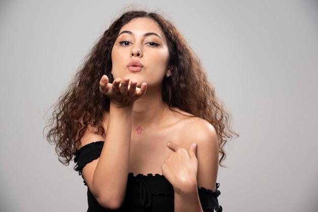 Giovane donna in camicetta nera che soffia un bacio d'aria. foto di alta qualità