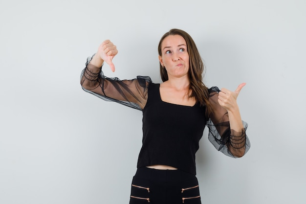 Young woman in black blouse showing thumb up and down and looking puzzled