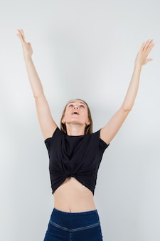 Young woman in black blouse stretching her arms while looking up and looking blissful