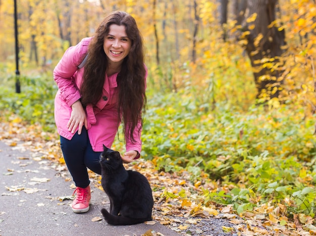 Young woman and a black cat in the autumn park