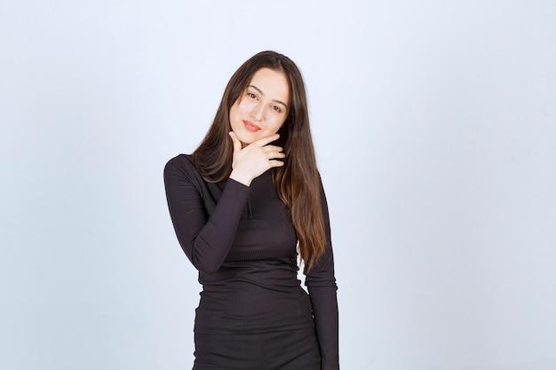 La giovane donna in vestiti neri sembra professionale e sicura