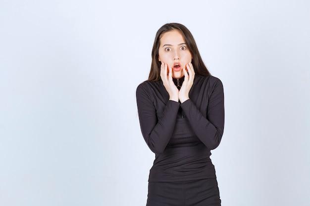 La giovane donna in abiti neri sembra terrorizzata e spaventata